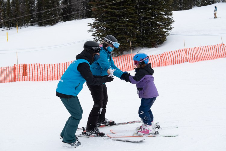 A girl skis with support from Rocky Mountain Adaptive staff.