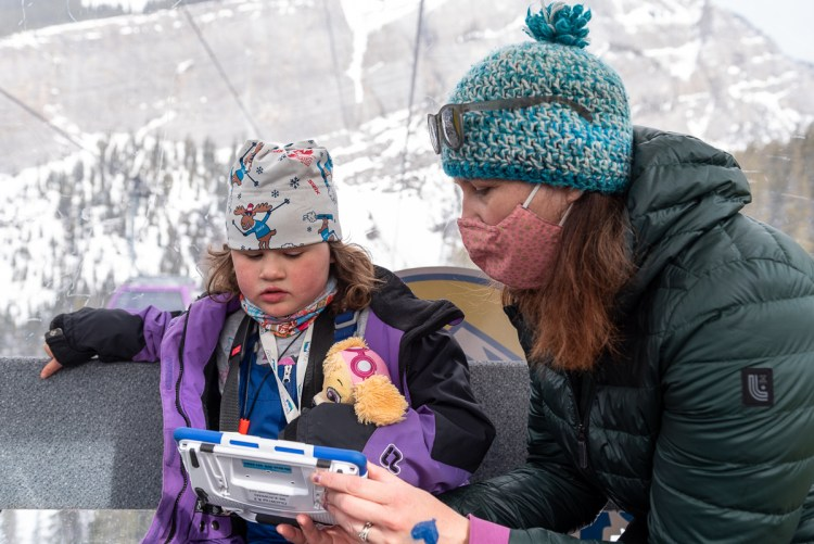 A mother communicates with her daughter using an assistive device while riding in a gondola.