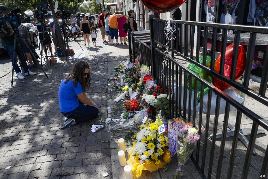 A mourner kneels at a makeshift memorial near members of the media outside the Hole in the Wall bar in the Oregon District in Dayton, Ohio, Aug. 5, 2019.