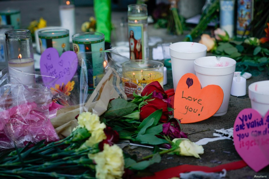 Candles burn as part of a memorial at the scene of Sunday morning's mass shooting in Dayton, Ohio, Aug. 5, 2019.