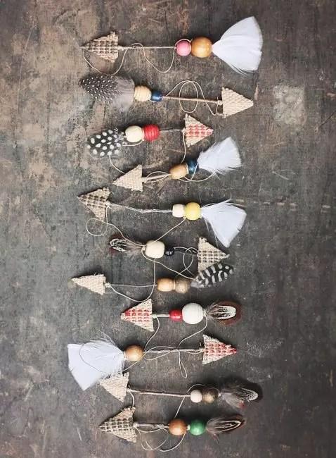 Украсить елку можно декоративными стрелами. Их изготавливают из веток, картона, бусин, пайеток и перьев