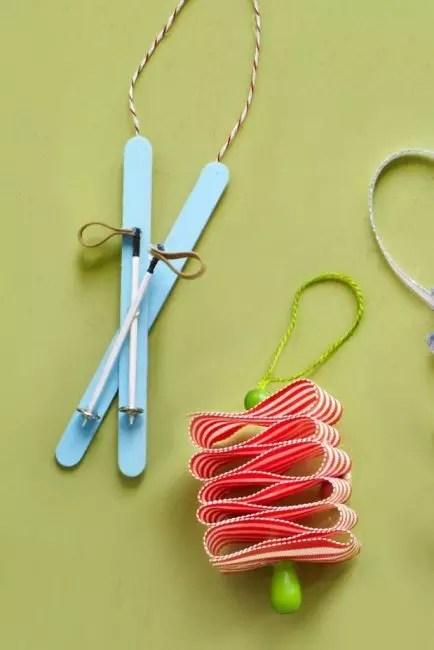 Лыжи на елке – самая новогодняя тема. Две палочки красят в голубой цвет, соединяют крест-накрест, фиксируют клеем. Лыжные палки делают из зубочисток, пуговиц и петель из кожи или шпагата. Собирают предмет в единое целое с помощью клея-пистолета
