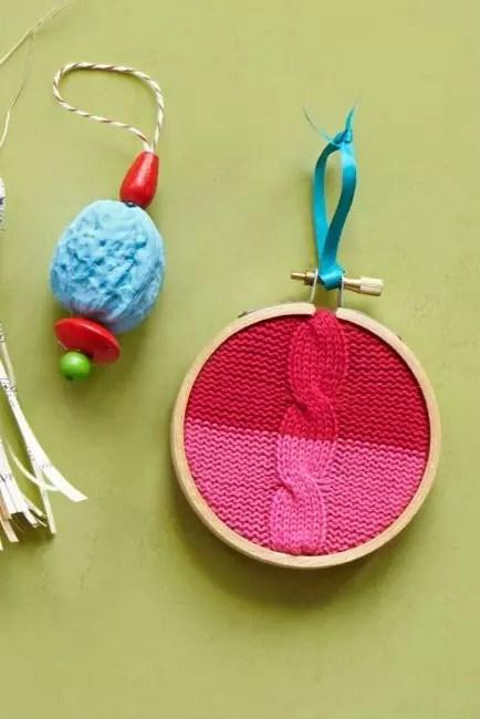 Деревянные пяльцы и старый детский свитер – прекрасно сочетаются друг с другом и еловыми веточками! Чтобы край вязаного полотна с обратной стороны не обсыпался, его обрабатывают клеем. Для подвеса используют яркую ленту