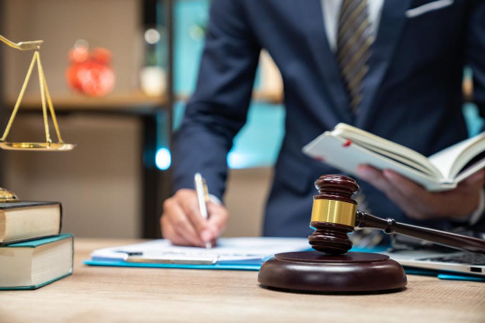 cerrar-abogado-empresario-trabajando-o-leyendo-libro-leyes-lugar-trabajo-oficina-concepto-abogado-consultor_35048-2062