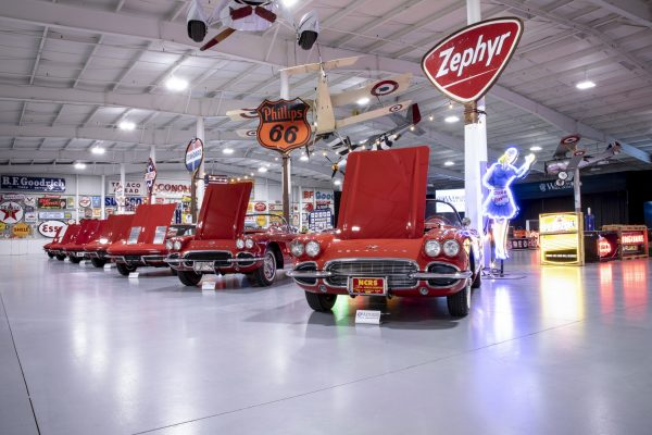 A row of red cars surrounded by vintage and neon signs.