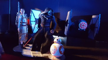 LEGO figures of Rey, Kylo, BB-8 are flanked by TIE fighters.