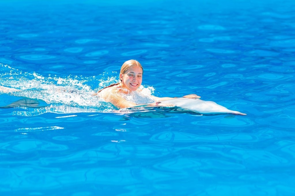 Happy little girl swimming with dolphins by Krystal International Vacation Club