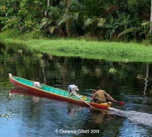 Man driving a brightly colored dugout canoe on a tropical river. Many of my adventures before writing happened on the rivers of Papua, Indonesia.