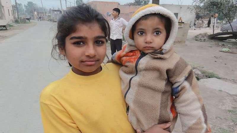 Mädchen mit Kleinkind auf dem Arm