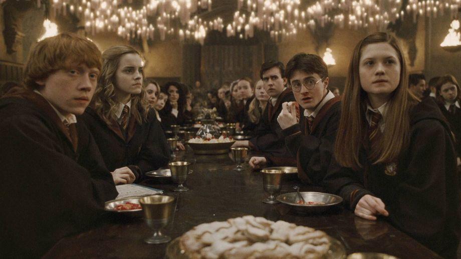Scéna jednoho z potterovských film. U nebelvírského stolu ve Velké síni sedí po levé straně stolu Hermiona a před ní Ron a z pravé strany vzadu Neville, Harry a před ním Ginny.