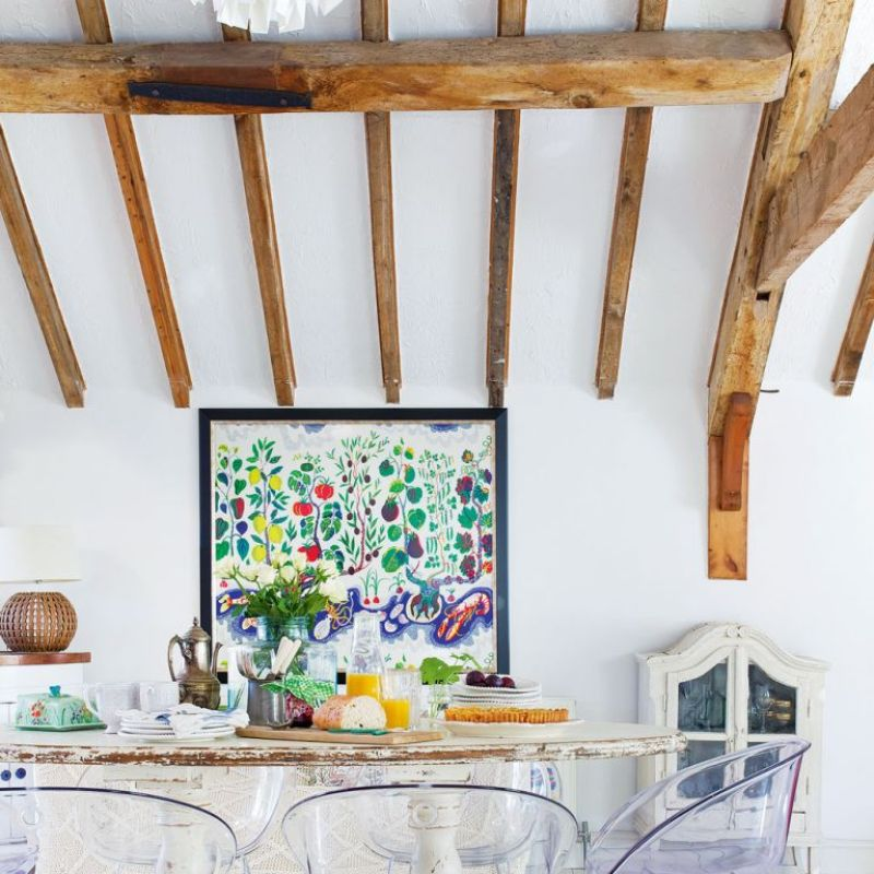 white dining room in barn with exposed wooden beams on ceiling