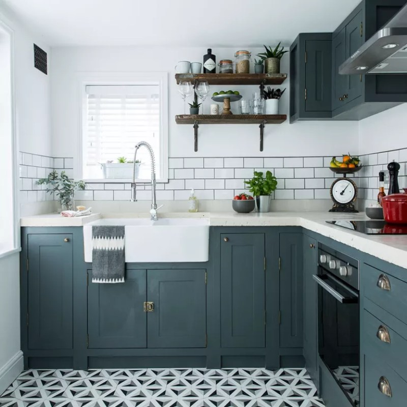 shaker kitchen cupboards with brass handles and decorative floor tiles and metro tile splashback