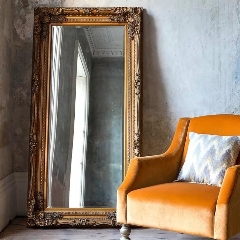 Dunelm Louis Gold Leaner Mirror beside orange velvet armchair