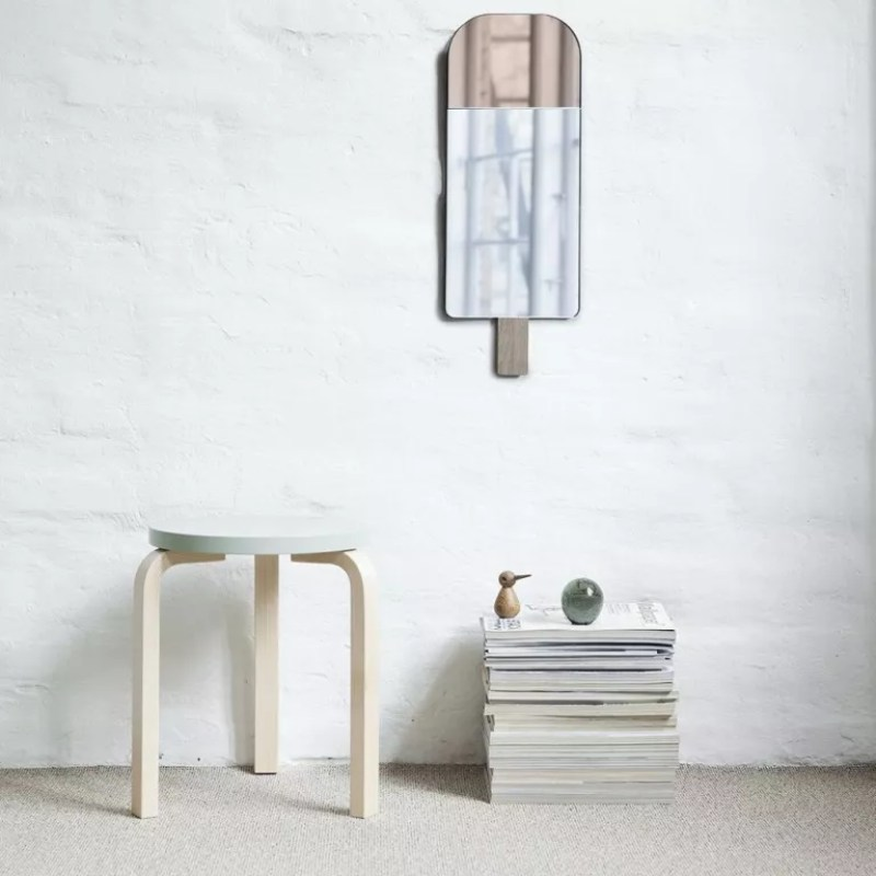 EO Ice Cream Mirror in room with white brick walls, magazines stacked underneath and side table