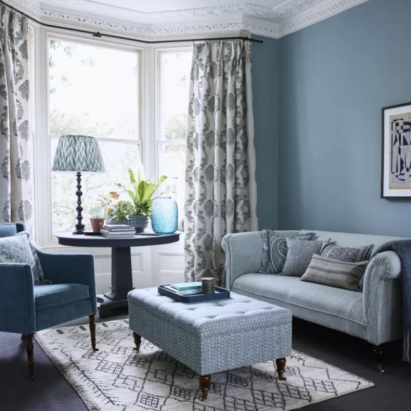 light blue living room with coordinating blue sofa and soft furnishings