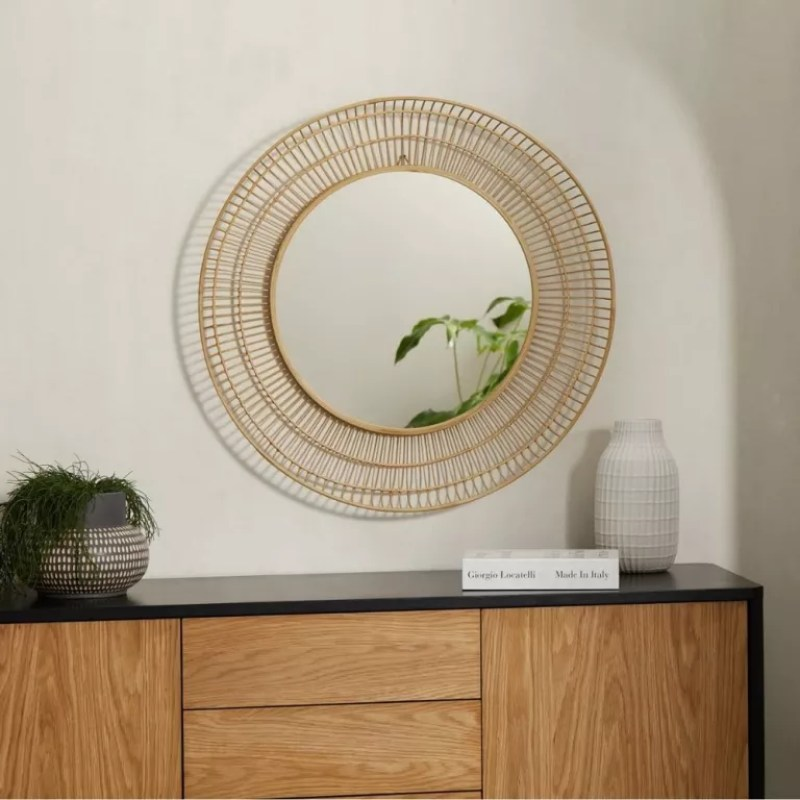 MADE Tulsi Bamboo Round Wall Mirror mounted atop sideboard with book, plant and vase underneath
