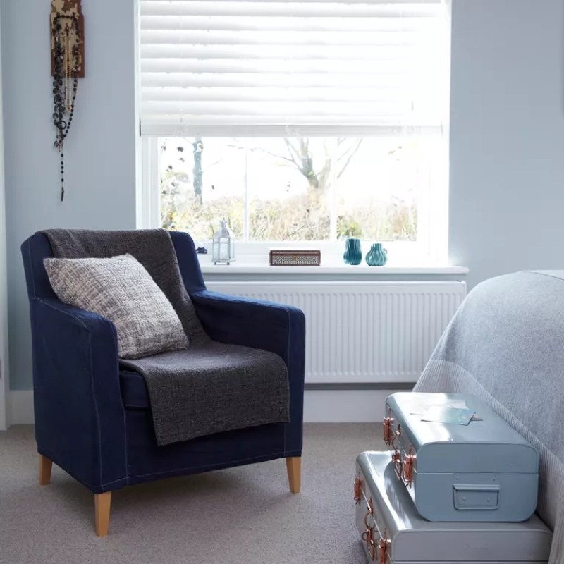 blue bedroom with occasional chair and storage boxes