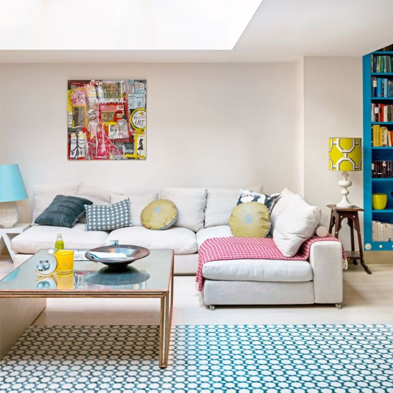 Extended living space with roof lantern over large l-shaped white sofa with blue bookcase and blue patterned rug