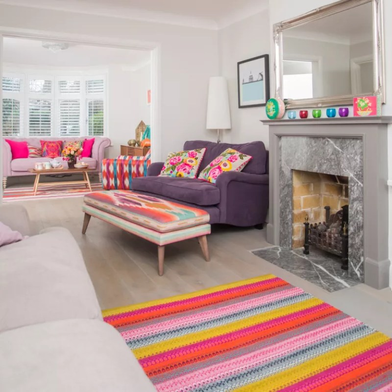 Large bright living room with colourful rugs and sofas