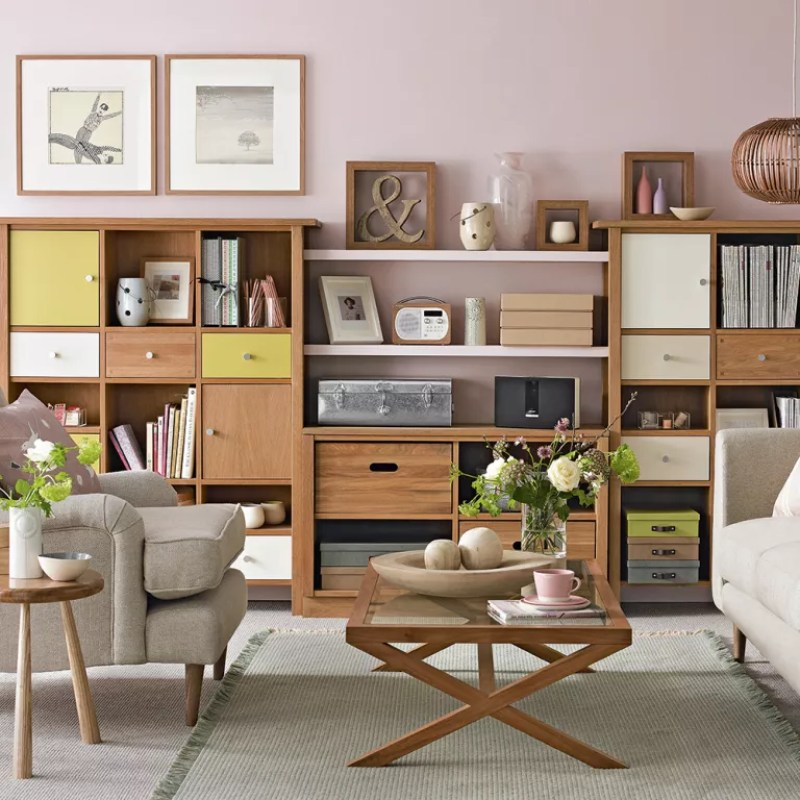 pale pink living room with wall of wooden storage