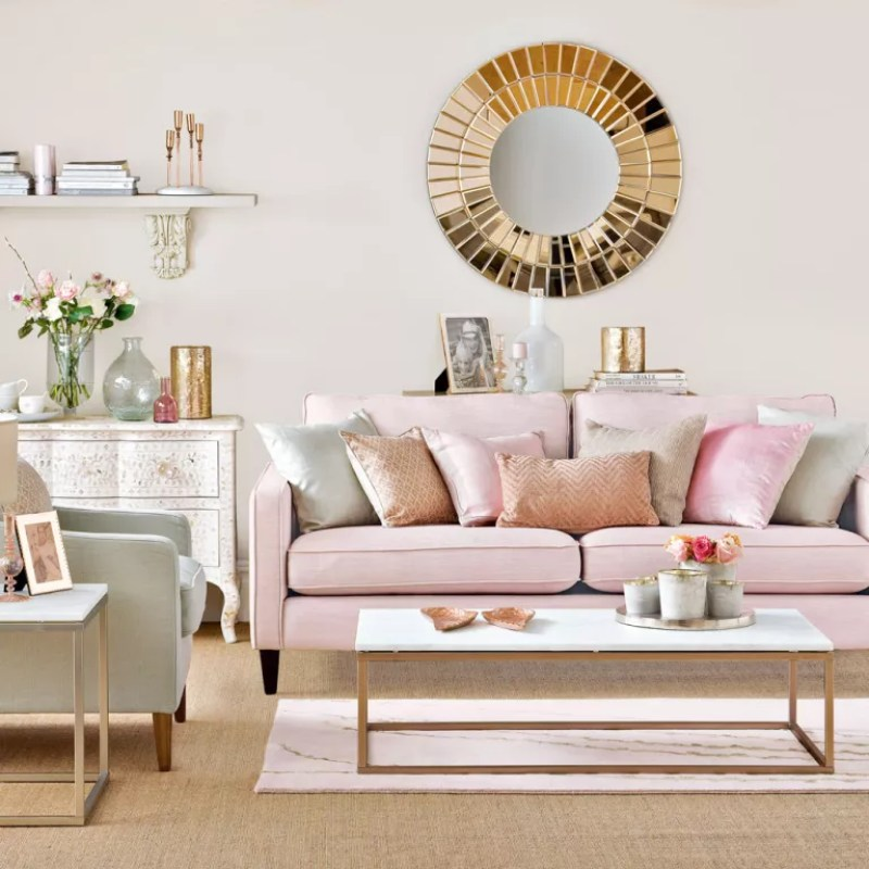 Neutral living room with pink sofa and gold round mirror