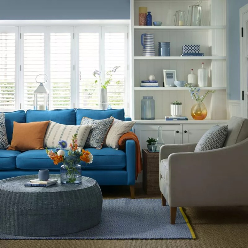 Blue living room with white built in shelving and white shutters