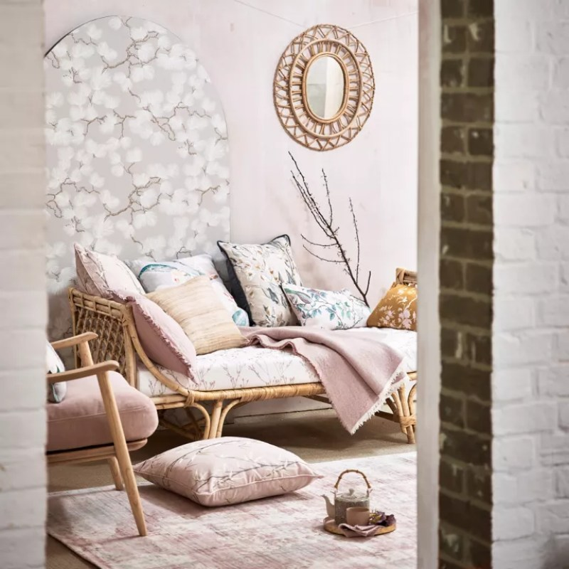 pink living room with blossom wallpaper panel behind chaise