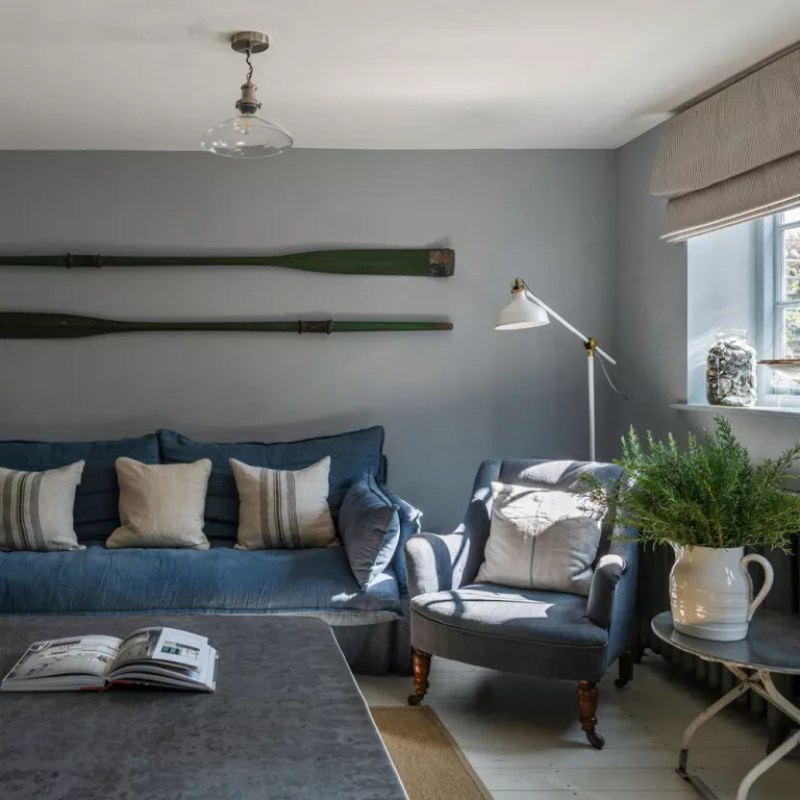 Coastal blue living room with grey walls blue upholstered sofa and armchair with glass ceiling pendant