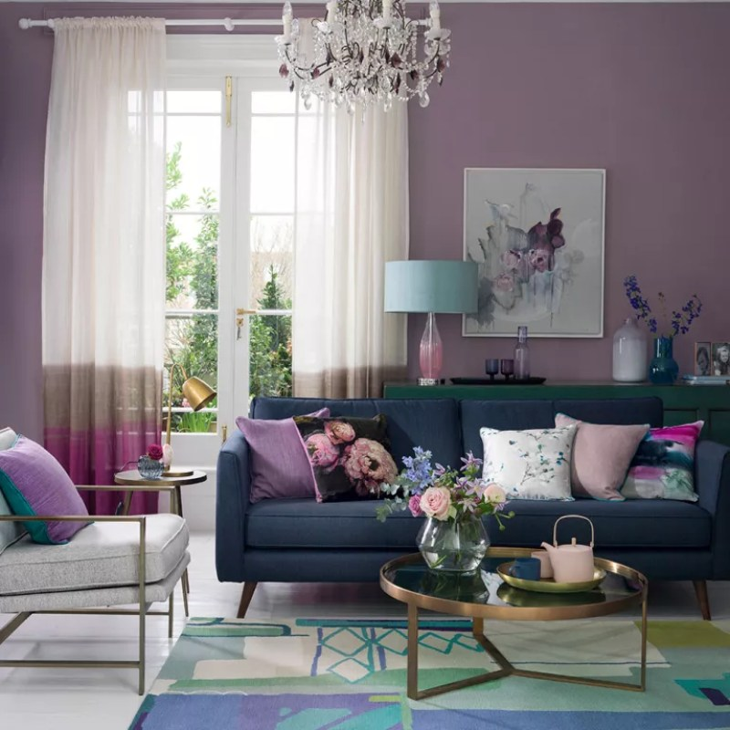 Purple living room with colourful patterned rug glass chandelier and dark blue sofa