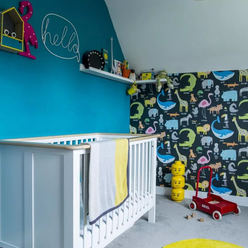 Nursery with turquoise wall and zoo animal wallpaper