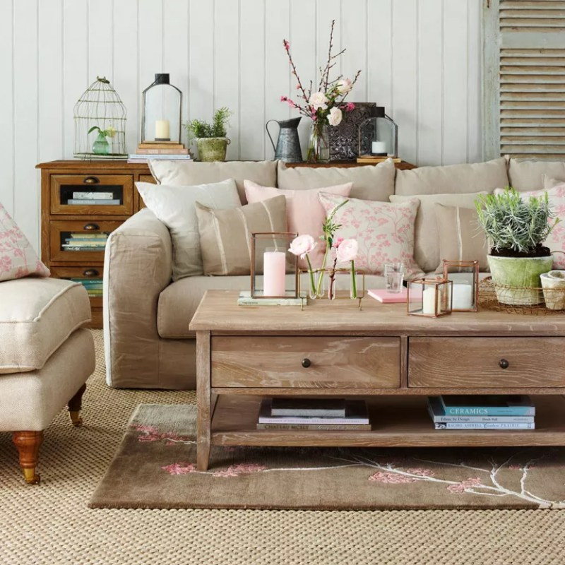 neutral living room with sofa loaded with cushions and low wooden coffee table