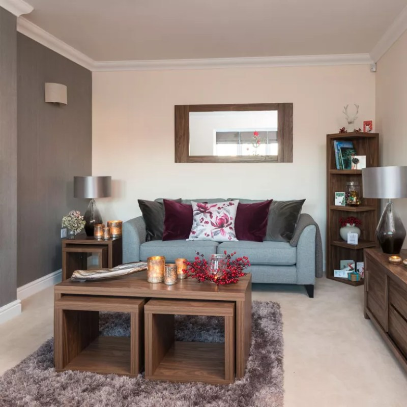 Living room with cream wall and brown wallpapered feature wall with duck egg blue sofa
