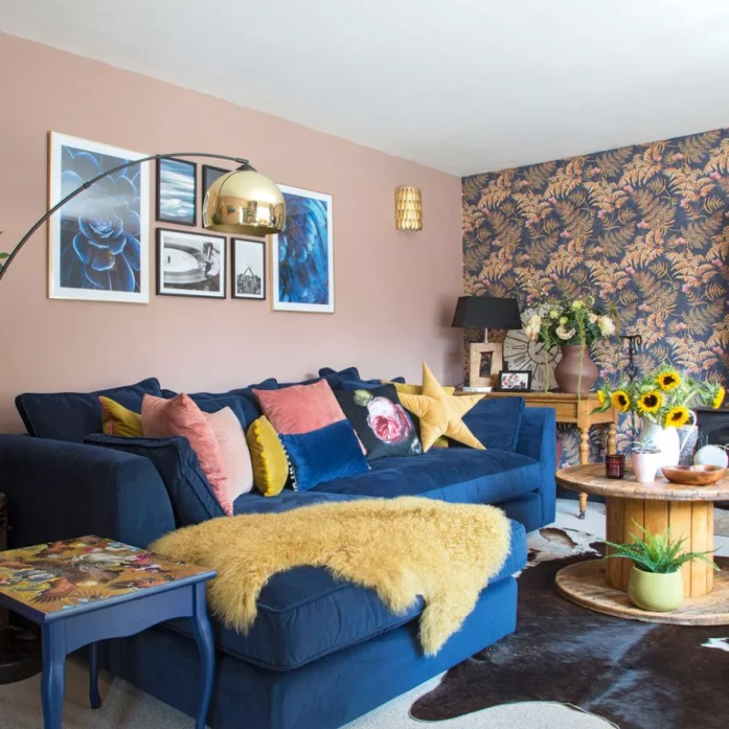 Pink living room with blue and pink wallpaper and blue sofa