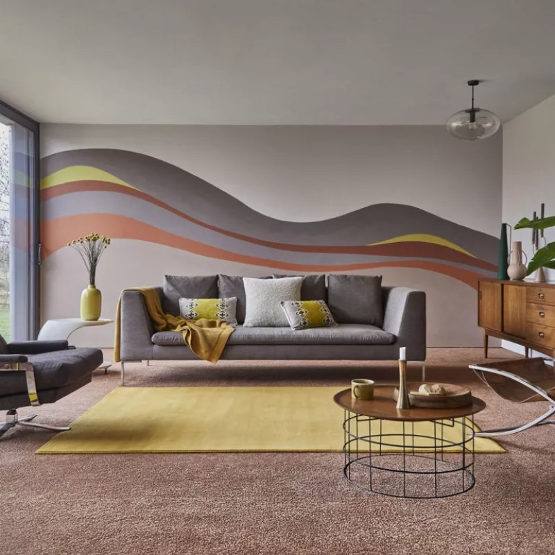 Living room with painted wall mural with coloured carpets