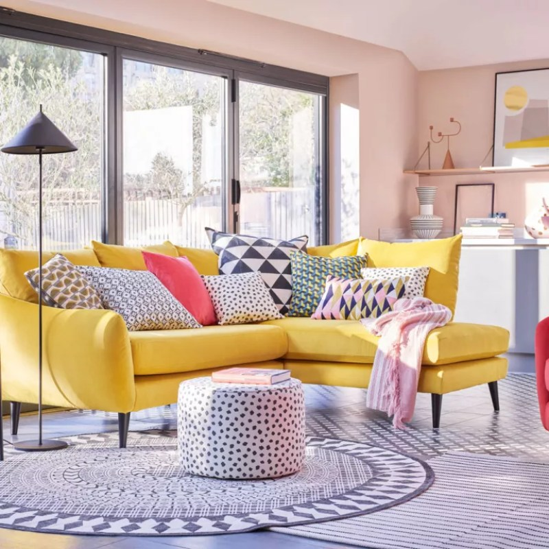 Pink living room with bright yellow l-shaped sofa