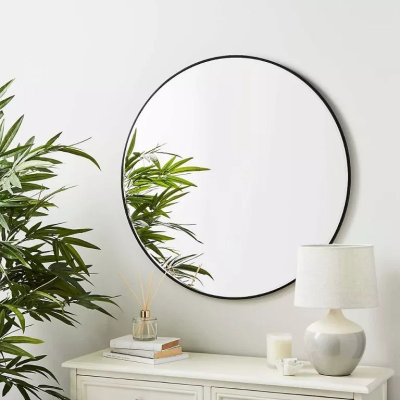 Dunelm round mirror with black frame wall mounted atop white sideboard next to large plant with books and lamp on side