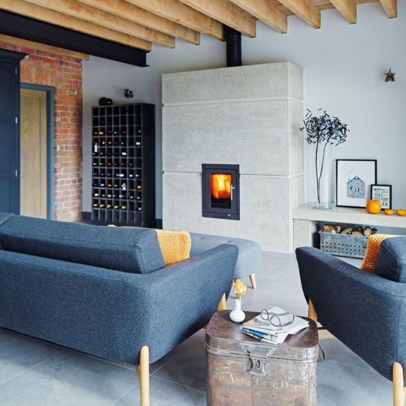an inbuilt wood burner with a concrete surround in a large open plan living room with blue sofa and wood beams - Brent Darby