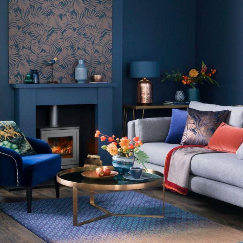 deep blue living room with rich metallic coffee table, log burner and grey sofa