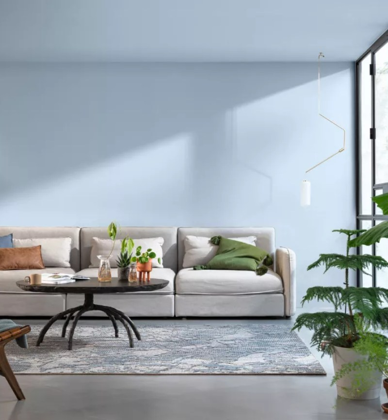 blue living room with pale blue walls and royal blue armchair beside white sideboard