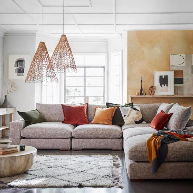 Living room with grey corner sofa and two woven pendant lights