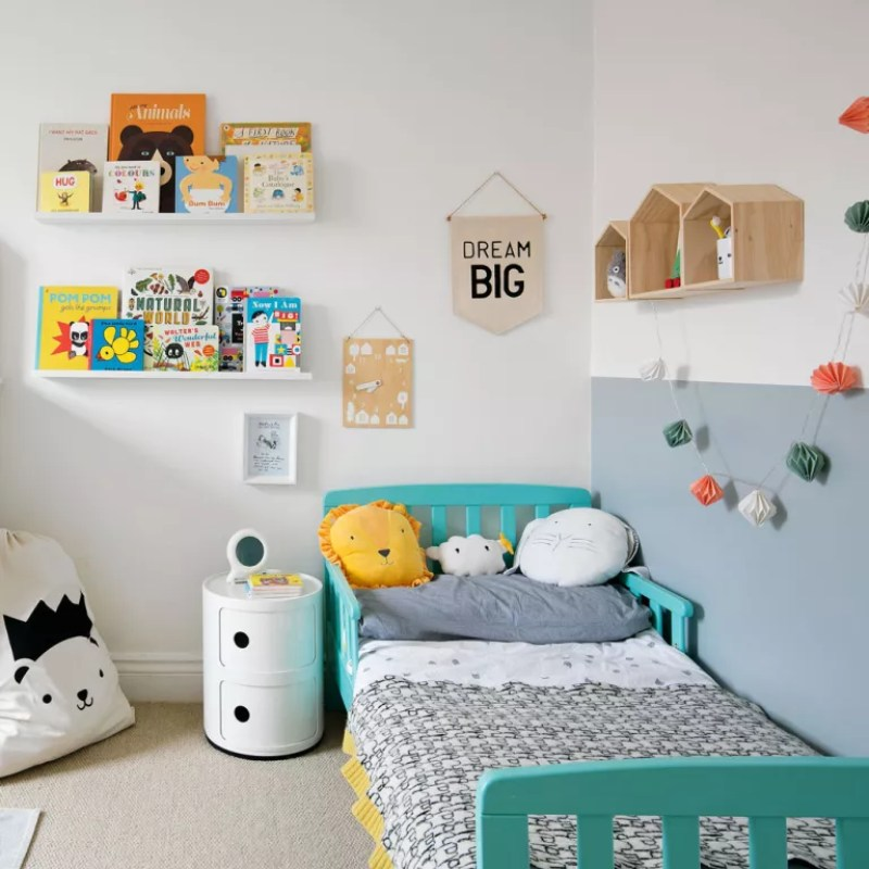 nursery with white and grey walls blue bed and book shelves