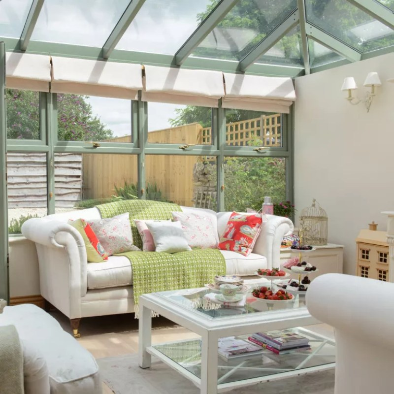 green conservatory with cream furniture