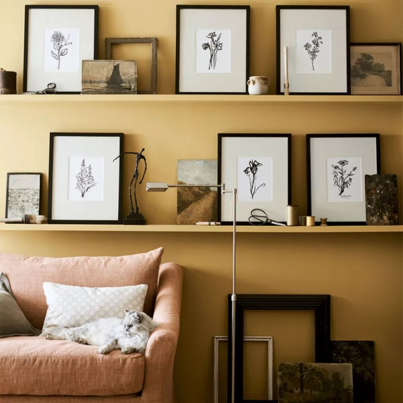 Living room feature wall with yellow walls and picture ledges