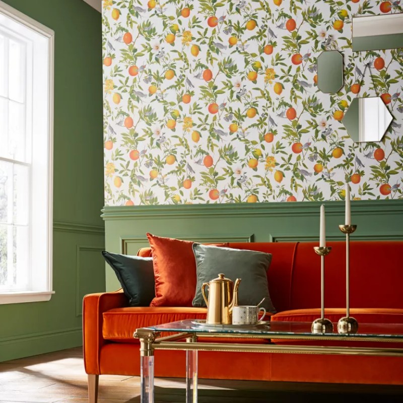 a burnt orange sofa with green wall panels and Amalfi Fresco wallpaper by Graham and Brown