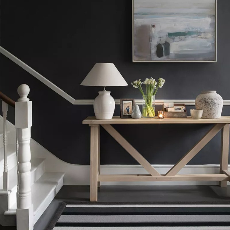 stairway lighting black hallway with wooden console and lamp