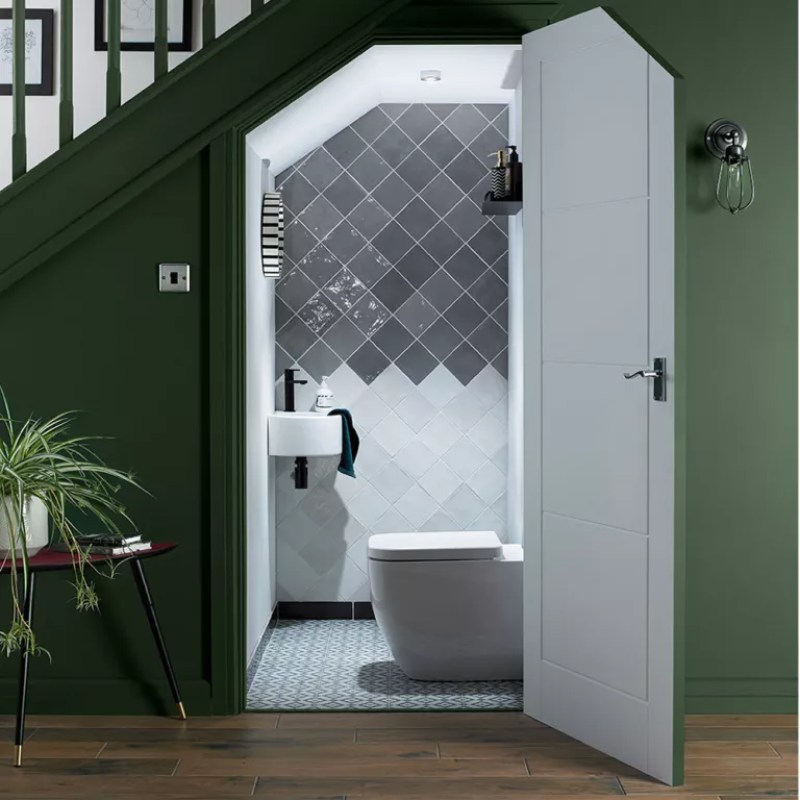 under stair toilet with grey and white tiles