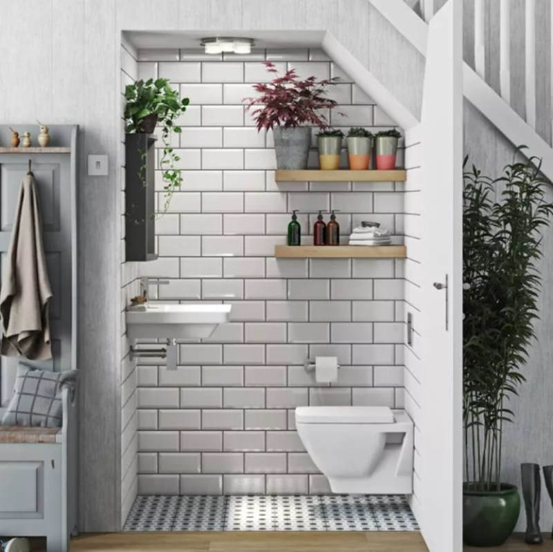 under stairs toilet with white tiles and plants