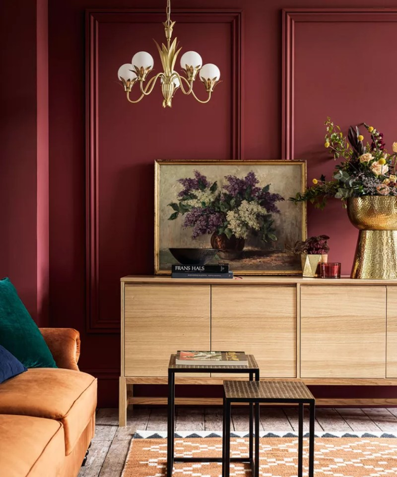 Living room painted red, with wooden sideboard and gold and glass chandelier