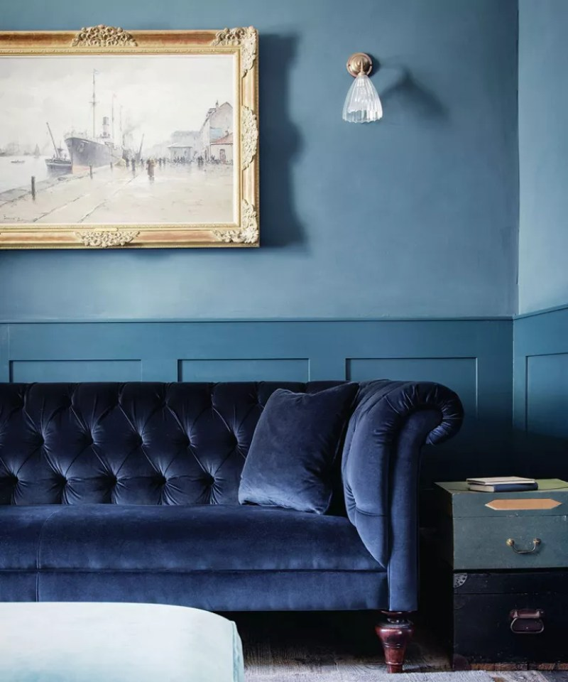 Blue living room with blue velvet sofa and small glass wall lights