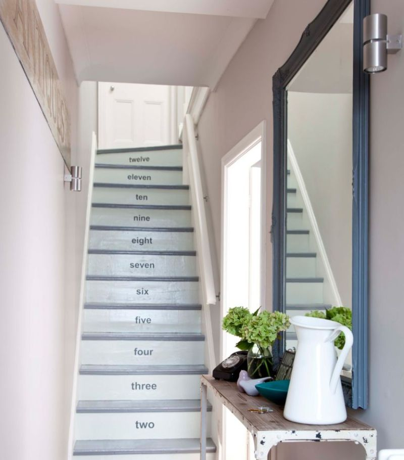 narrow hallway with numbered stairs slim console table and large mirror